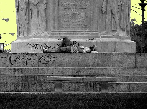 A man sleeps at the foot of the Illinois Centennial Monument in Logan Square. (Photo by M. Jeremy Goldman / Flickr)